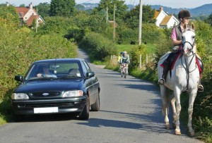 car overtaking horse and rider