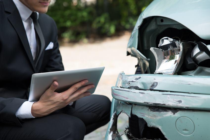 insurance agent checking damaged car